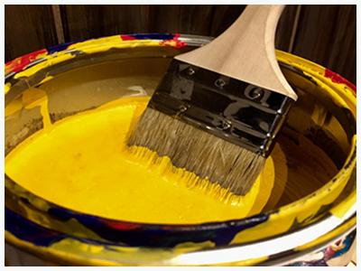 黄色いペンキ缶に入った刷毛